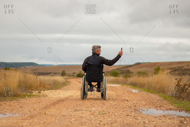 Rear vision of a disabled man in wheelchair in a path taking a selfie