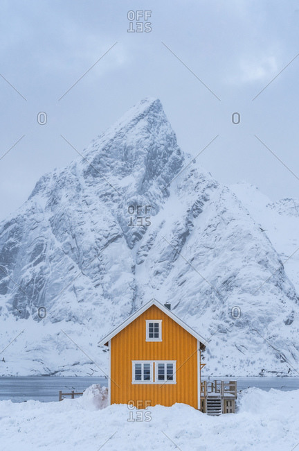 Lonely house with a sharp edged mountain in Lofoten Islands