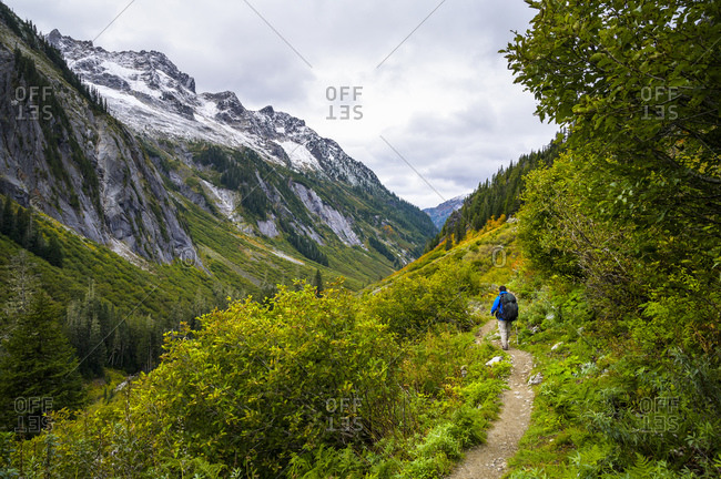 Male hiker walking on trail through the mountains