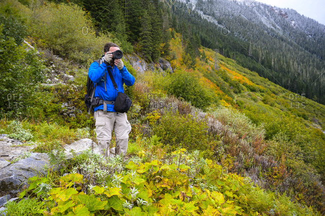 Photographer on hiking trail with blue jacket