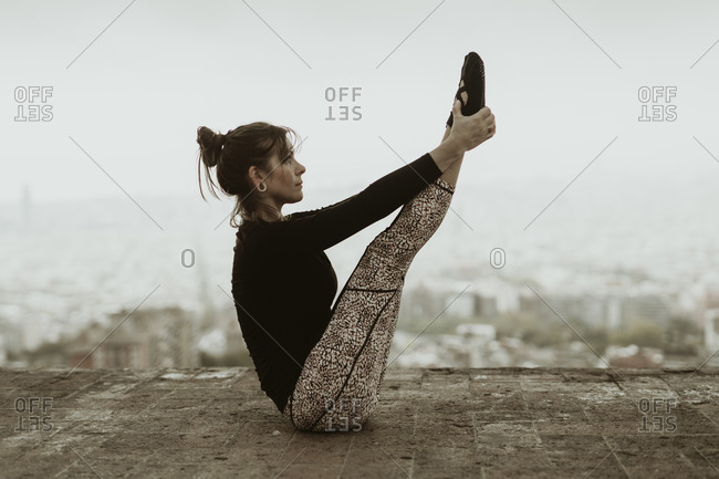 Young woman practicing yoga, she grabs her legs with her arms