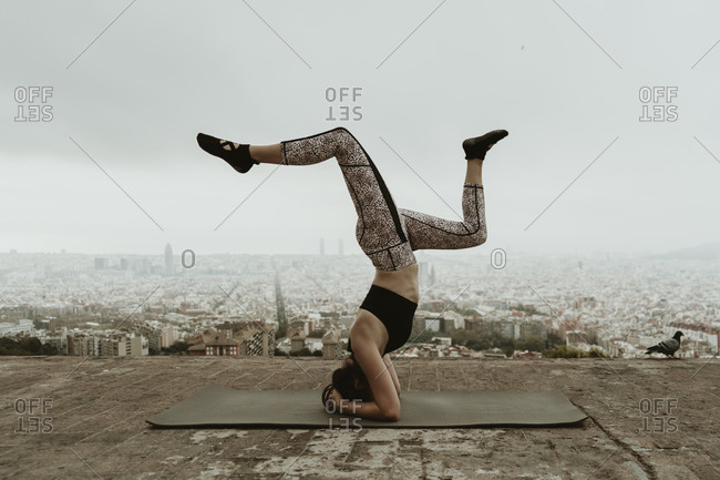 Young woman practicing yoga, asana with legs lifted. .