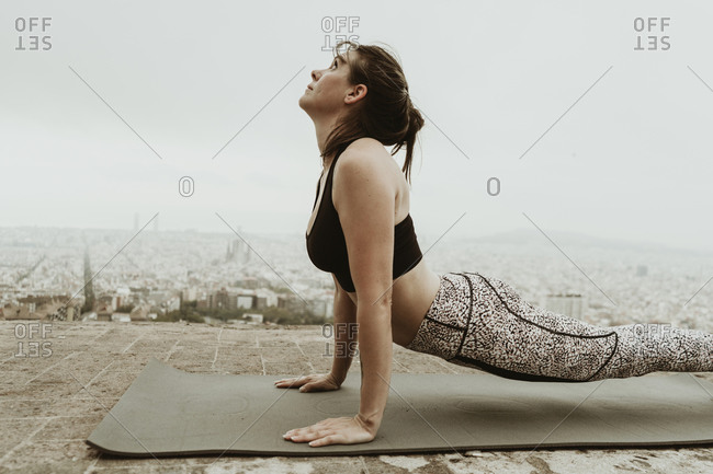 Young woman practicing yoga, back stretching.