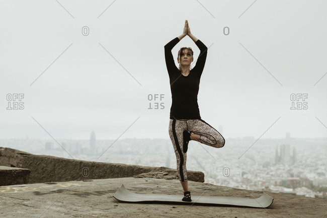 Young woman practicing yoga, arms raised looking up.
