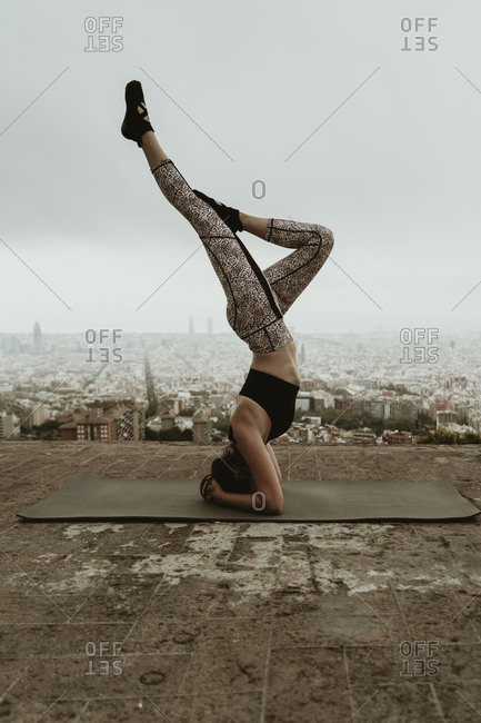 Young woman practicing yoga, asana with legs raised.