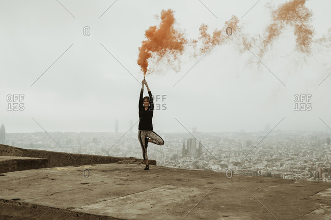Young woman practicing yoga, with an orange flare in her hand