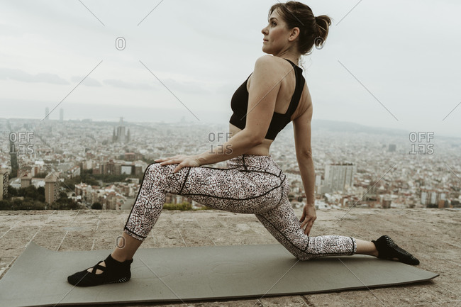 Young woman practicing yoga, stretching.
