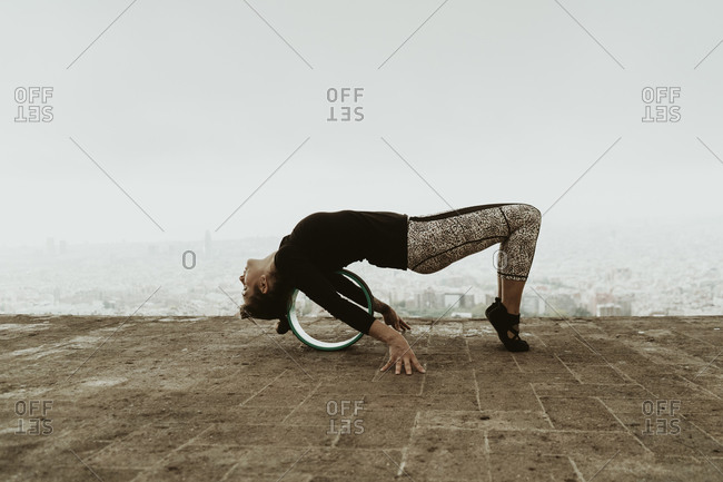 Young woman practicing yoga, stretching her back with a roller.