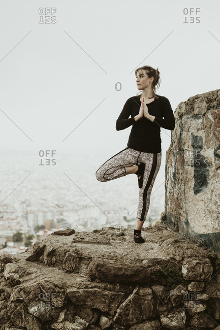 Young woman practicing yoga, asana looking at the city