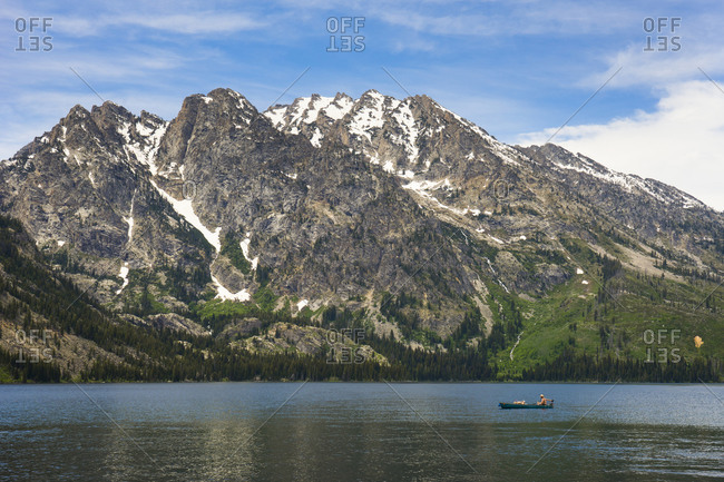 Person in a canoe fishing in jenny lake, mountains behind
