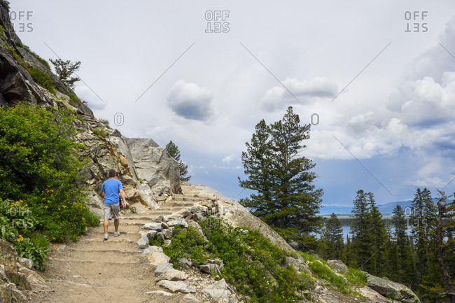 Man hiking cascade canyon trail to inspiration point at Jenny Lake