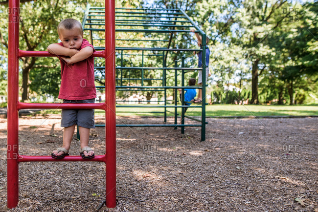 Young boy looking sad on playground while older boys climb behind him