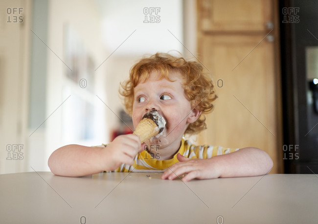 Messy toddler boy eats ice cream while sitting at counter in kitchen