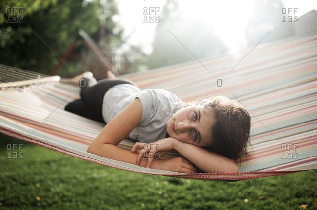 Tween girl looking while laying in hammock in backyard on spring day