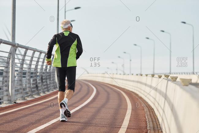 Unrecognizable elderly man running along track