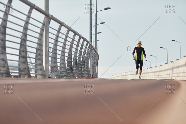 Modern elderly man jogging long shot