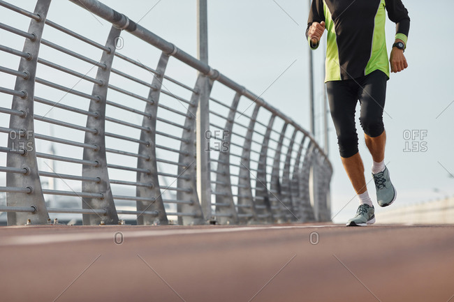 Unrecognizable active old man jogging along track