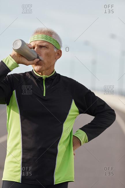 Senior sportsman drinking water