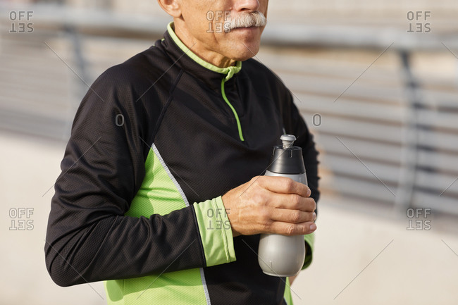 Sporty senior man with bottle of water
