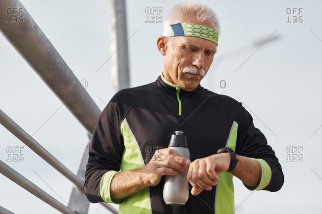Senior sportsman checking time