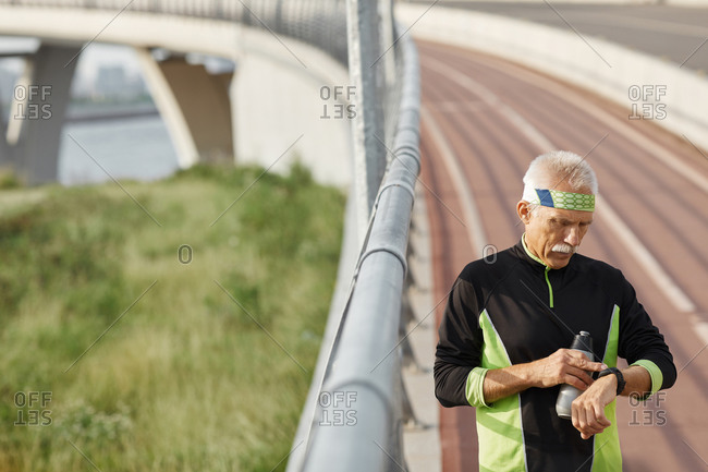 Sporty aged man checking time