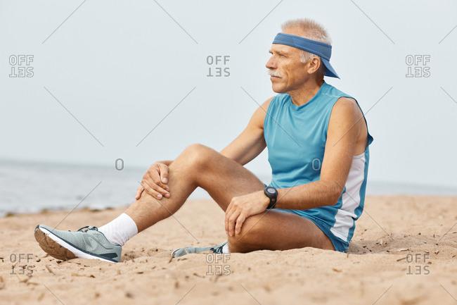 Senior man in sportswear relaxing on beach