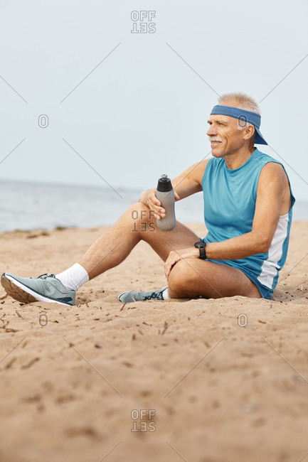 Sporty senior man relaxing with bottle of water