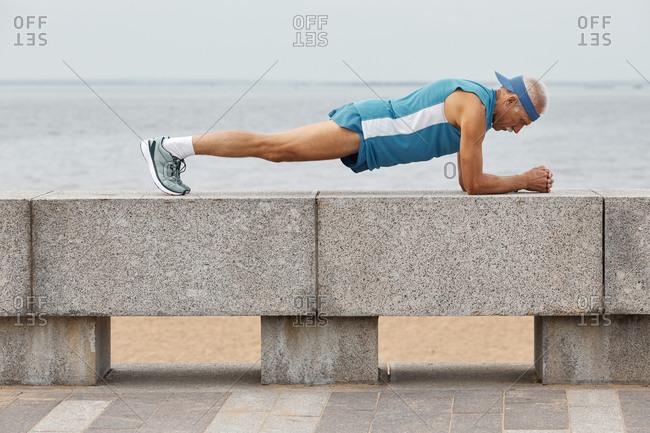 Senior sportsman doing plank exercise