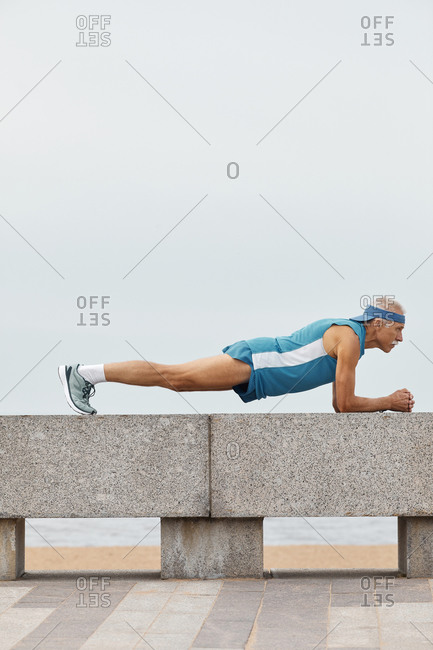 Strong senior man doing plank exercise