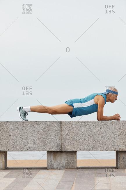 Strong senior man doing plank exercise