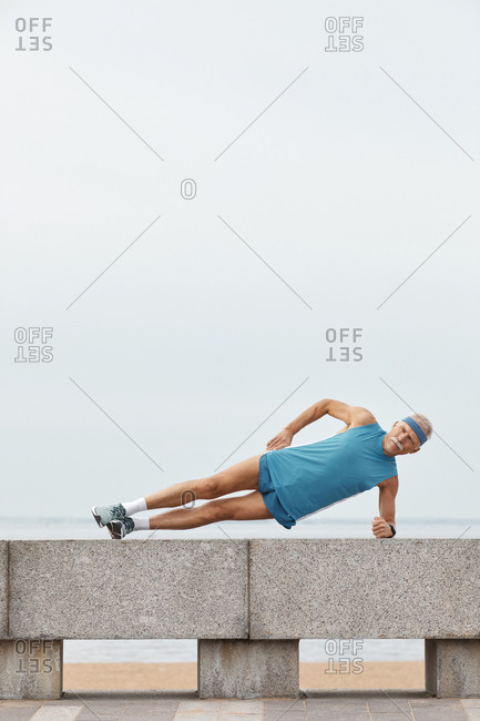 Aged sportsman doing side plank