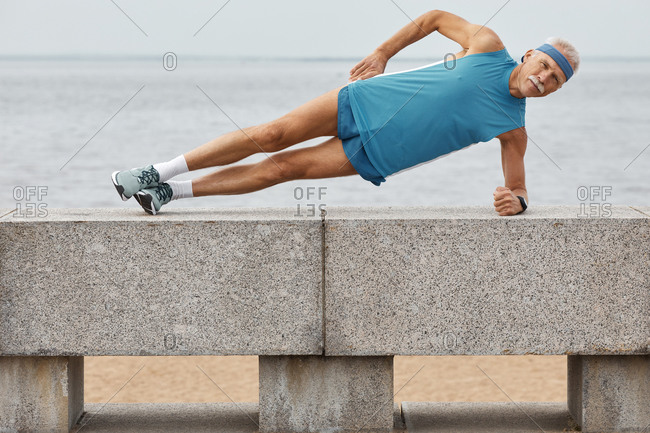 Strong aged man doing side plank