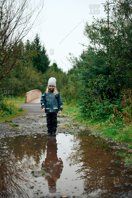 Girl motionless standing at edge of puddle in forest
