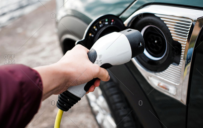 Hand holding a lead towards an electric car socket