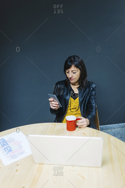 Woman with coffee and smartphone in her office
