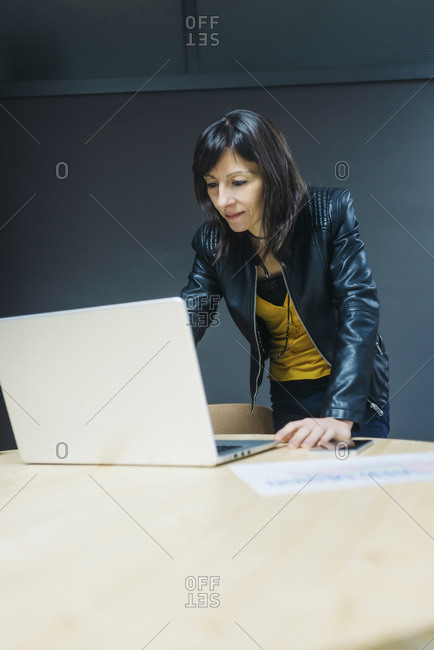 Female business executive looking at laptop in office