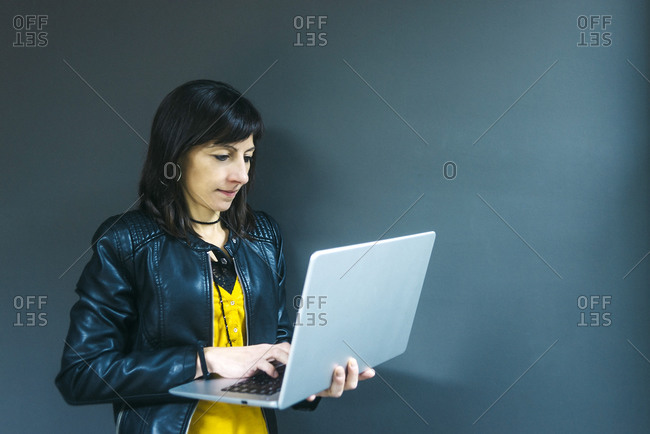 Fashion business woman working on laptop while standing against