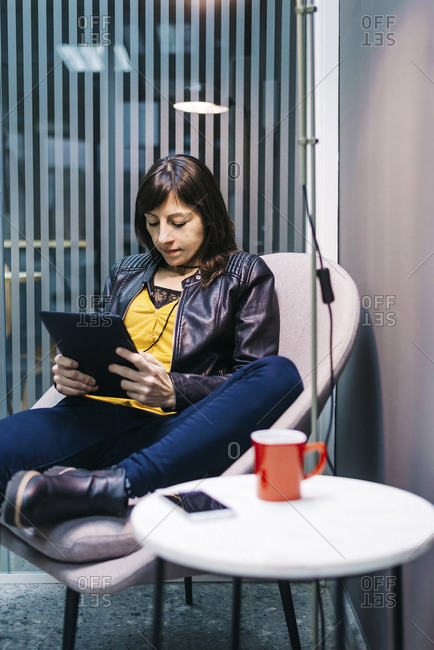 Woman at home sitting on modern chair and using tablet computer