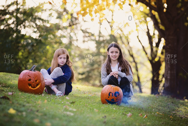 Two young girls sitting outside by smoking pumpkins in the fall
