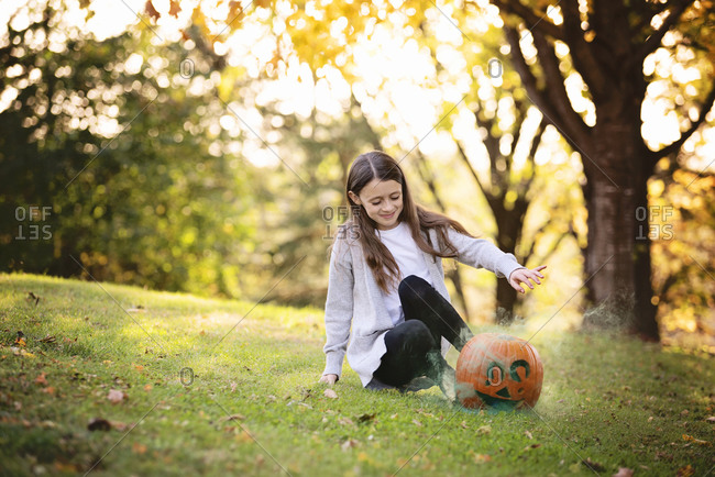 Young girl sitting outside with smoking pumpkin in fall
