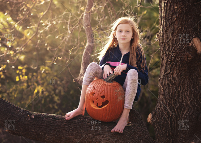Red haired girl in tree with pumpkin