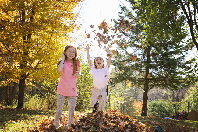 Two young girls playing in fall leaves