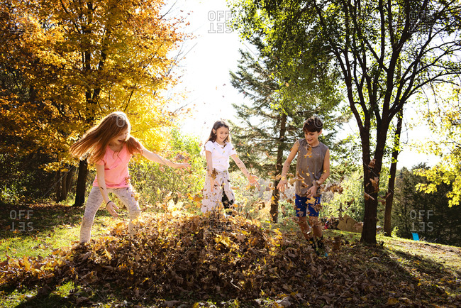 Three young friends playing outdoors in fall leaves