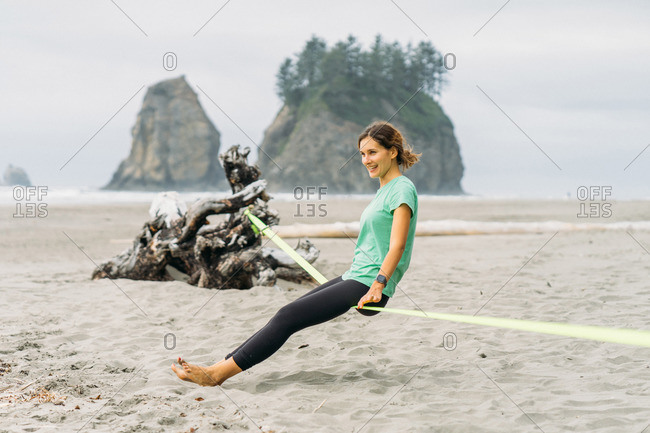 Girl is sitting on slackline at La Push beach in Olympic National Park