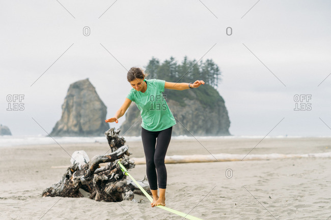 Girl is trying slackline at La Push beach in Olympic National Park