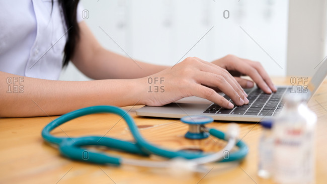 Close up doctor examining medical report while using tablet
