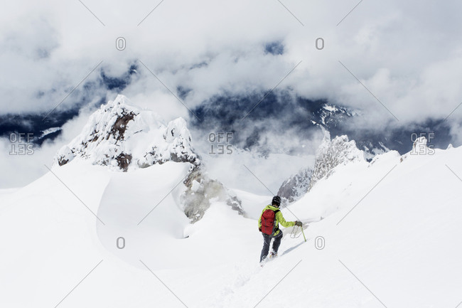 A young man descends from the summit of Mt. Hood on a cloudy day.