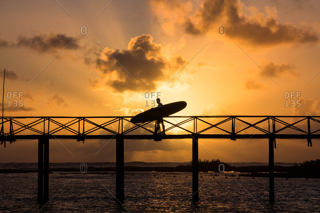 Silhouette of a man carrying a surfboard on cloud nine bridge