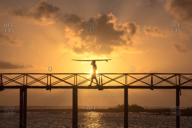 Man carrying surfboard on bridge of cloud 9 siargao, philippines