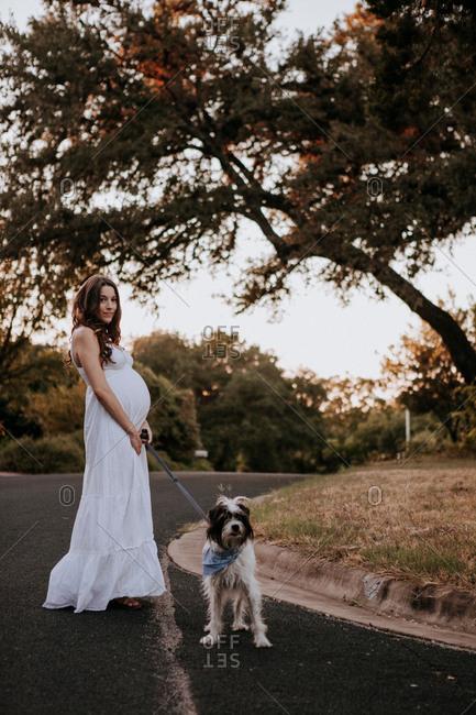Pregnant woman white dress walking her dog